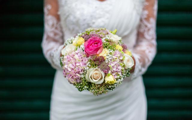 Hochzeitsfotografie Frau hält Blumenstrauss mit beiden Händen als Nahaufnahme