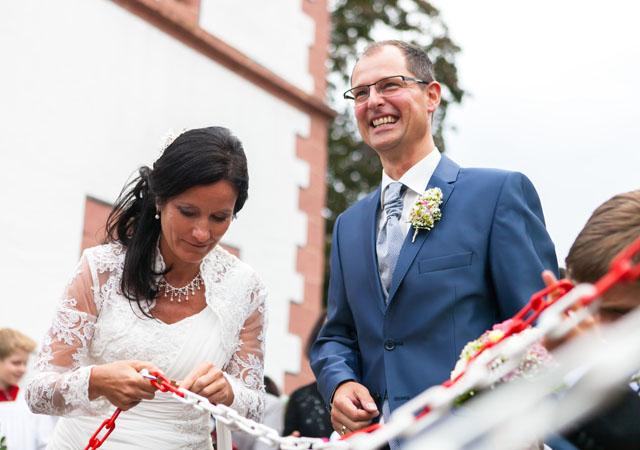 Dynamische Weitwinkelaufnahme aus Hochzeitsfotografie Reportage eines Paares das gerade ein Schloss öffnet
