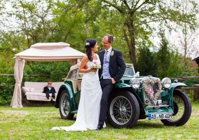 Hochzeitspaar angelehnt an grünem Oldtimer vor grüner, romantischer Natur Kulisse